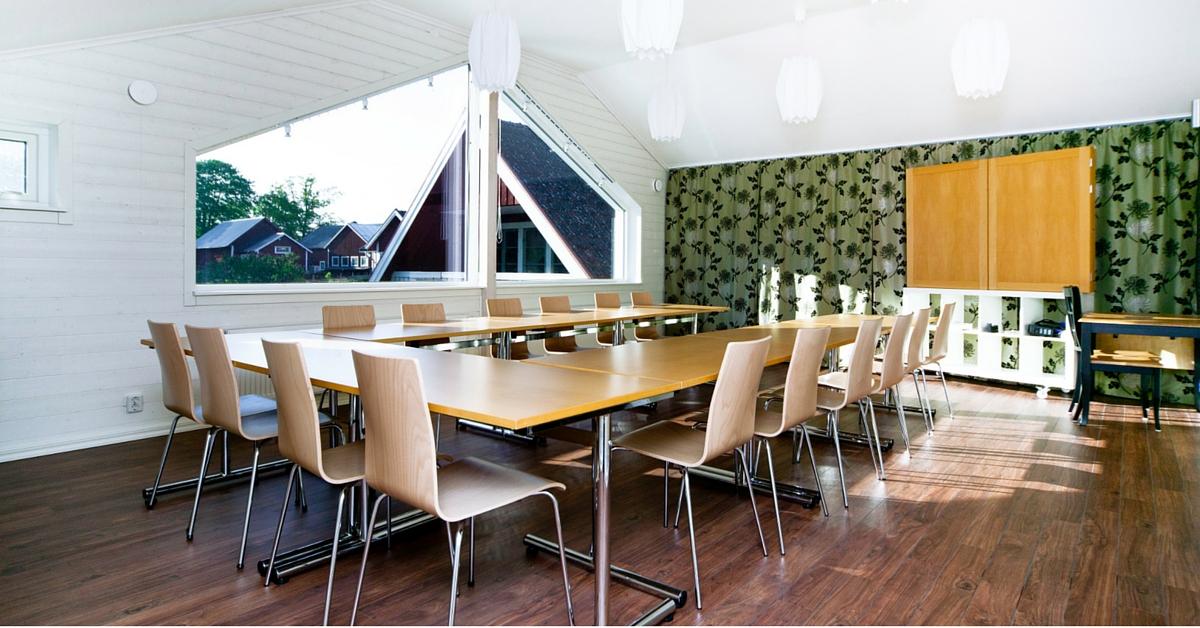 Ljus konferenslokal med bord och stolar uppställda som ett u.