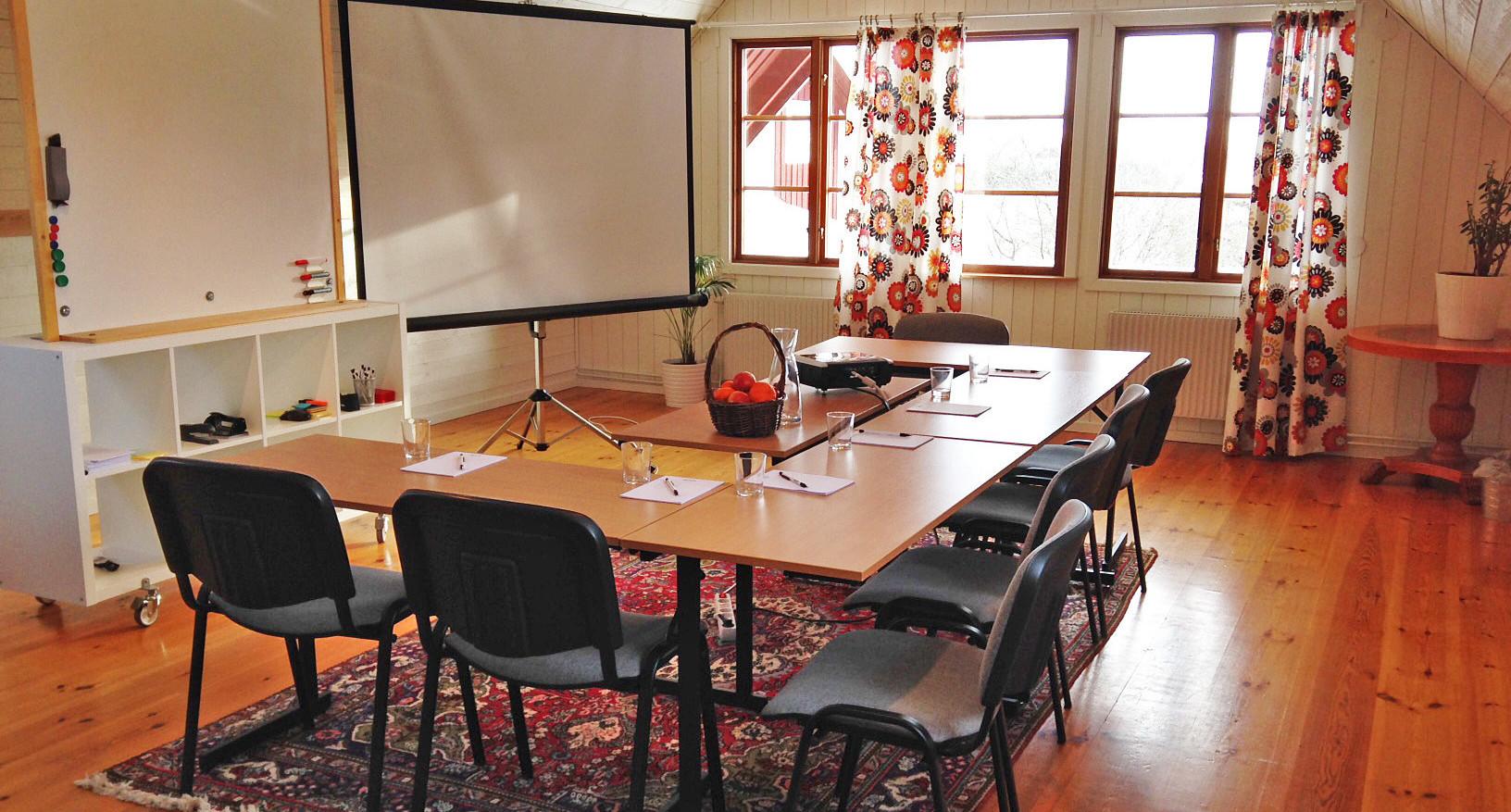 Litet konferensrum med bord och stolar samt projektorduk
