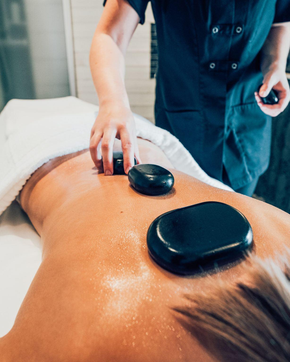 Terapeuts lägger svarta stenar på ryggen på en person som ligger på mage