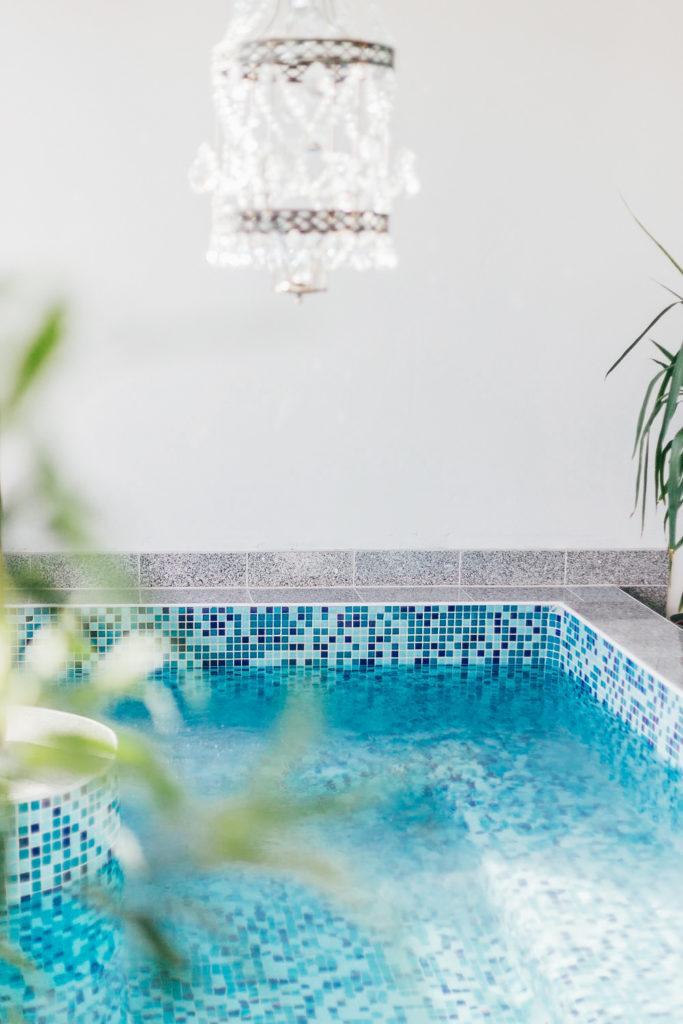 Inomhuspool med blå mosaikplattor. I taket hänger en kristallkrona.