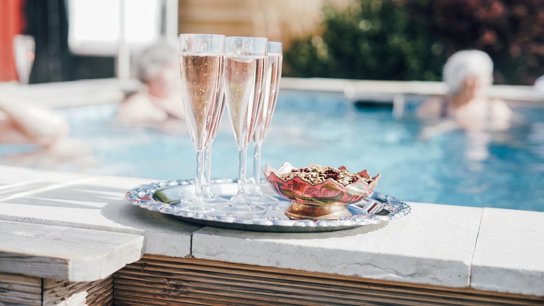 Bricka med champagneglas och tilltugg står på en poolkant