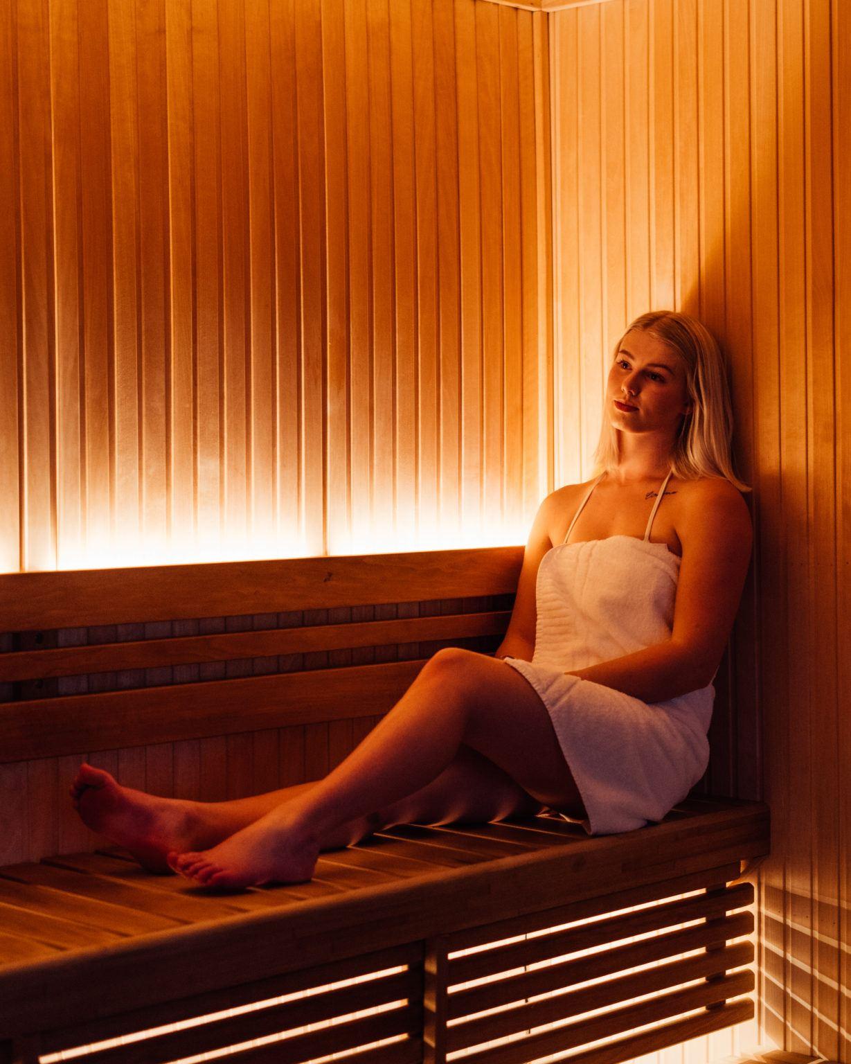 En kvinna sitter i handduk i en bastu med dämpad belysning
