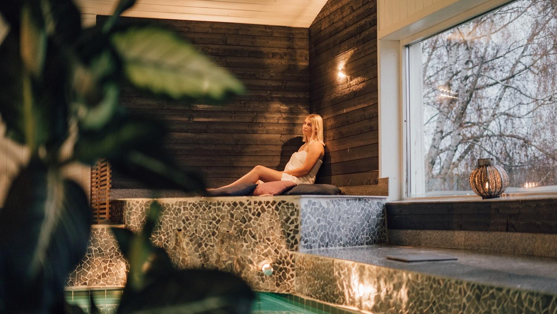 En kvinna iförd handduk sitter i spa-avdelning