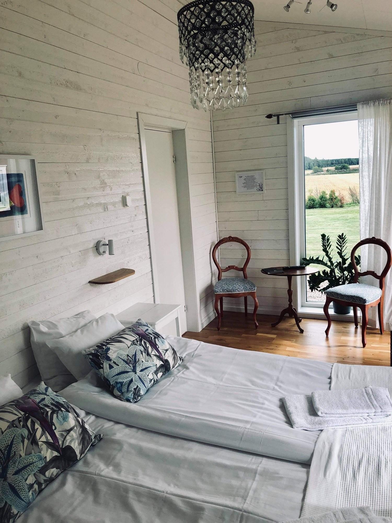 Ljust rum med vit väggpanel. I bilden syns sängar och en stol.