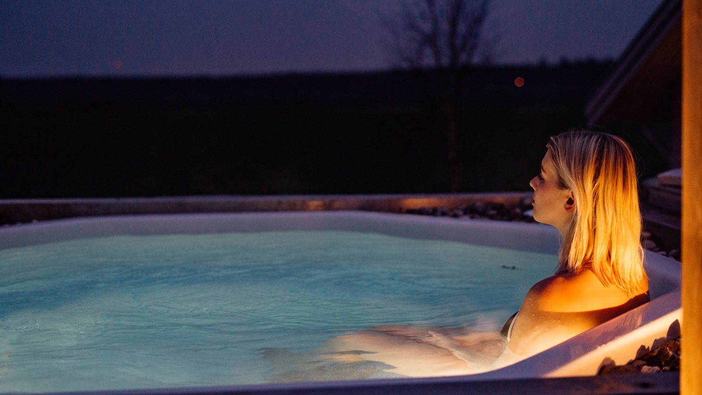 En kvinna sitter i en pool utomhus under kvällstid och ser avslappnas ut.