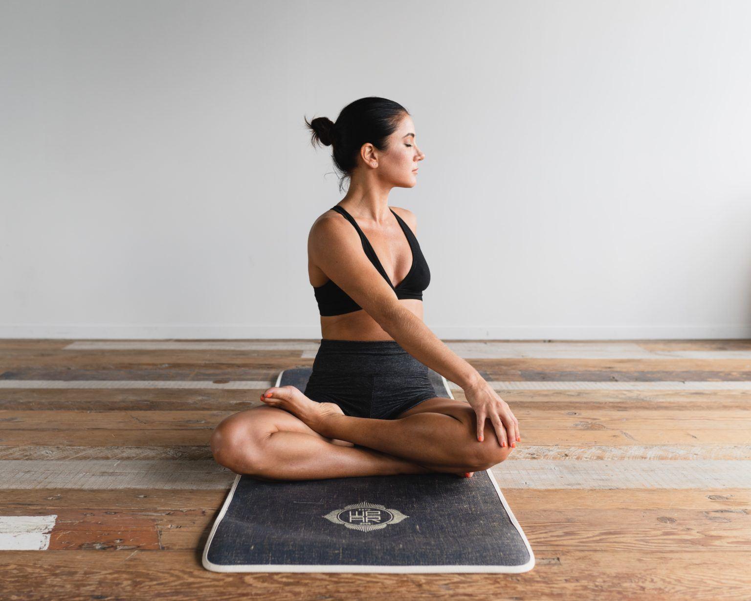 Kvinna med uppsatt hår sitter i yogaposition på en svart yogamatta.