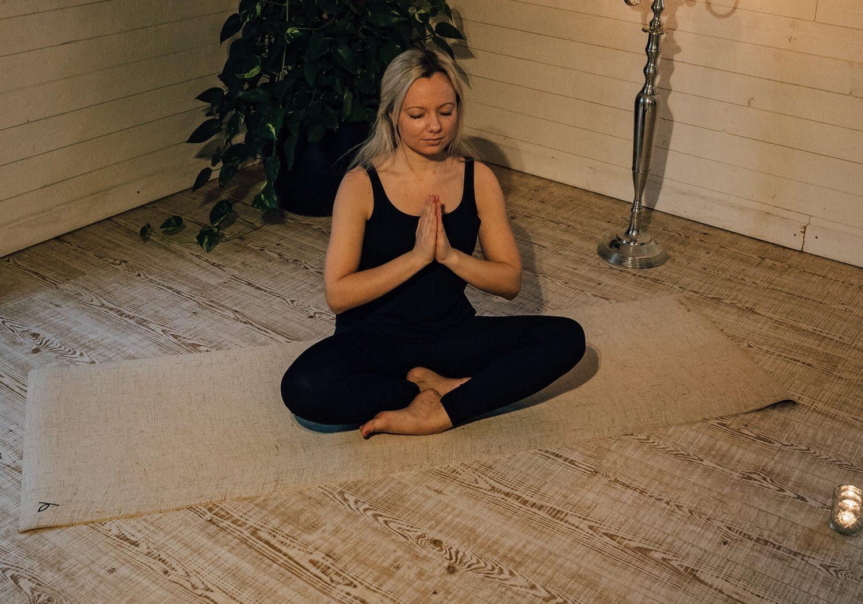 En kvinna i svarta kläder sitt på golvet i en yoga-pose.